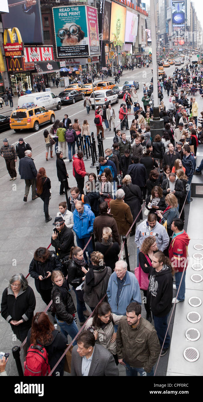 People line up for discount theater tickets in Times Square in New York City. - Stock Image