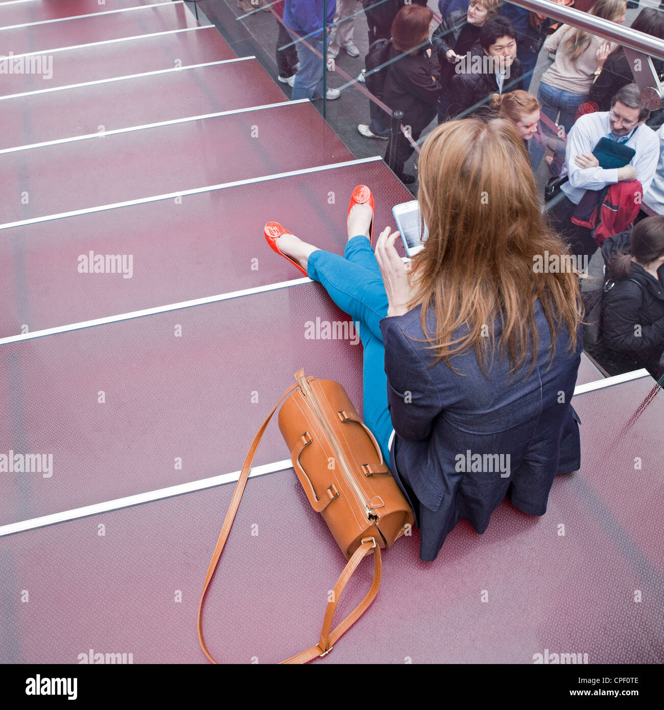 A woman spends a quiet moment with her phone before joining the crowds in Times Square in New York City. - Stock Image