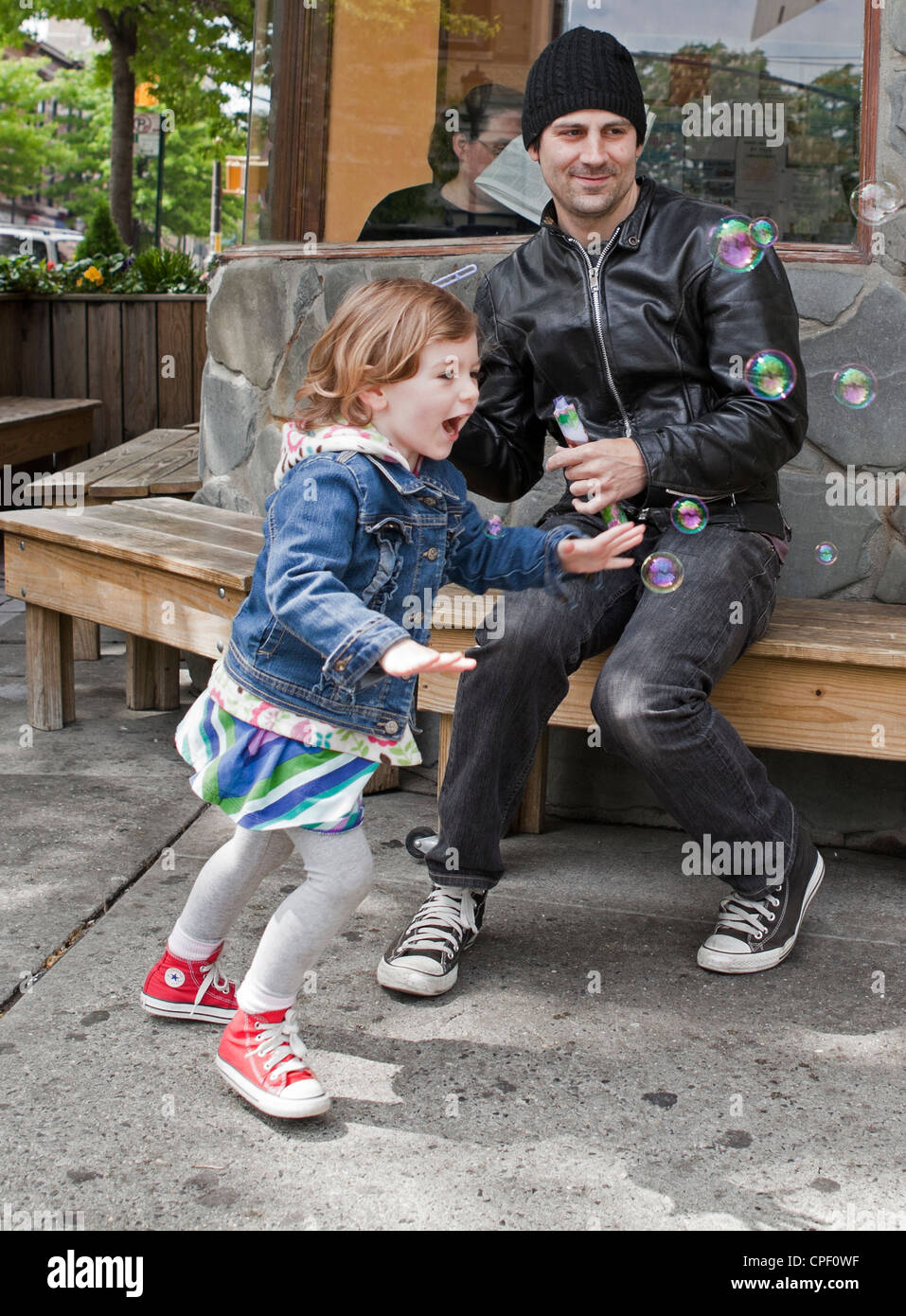 A father and daughter share time by blowing and chasing bubbles on a Sunday morning in Brooklyn. - Stock Image