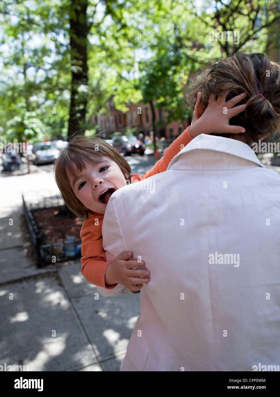 A mother and son bond on a sidewalk in Brooklyn. - Stock Image