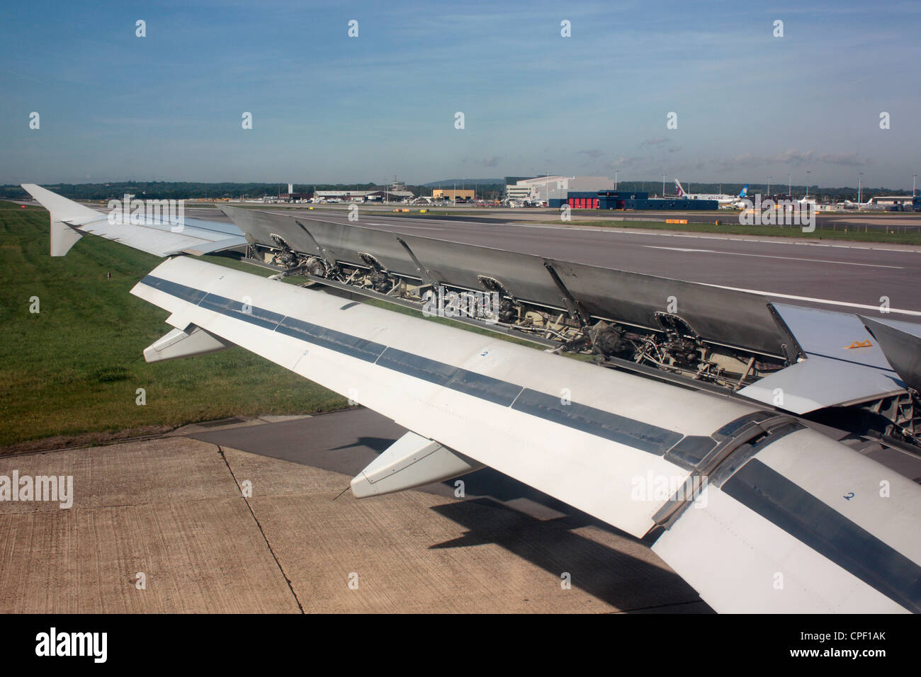 Commercial air transport. Wing of an Airbus A320 jet plane after touchdown with spoilers up and flaps down. Aerodynamics - Stock Image