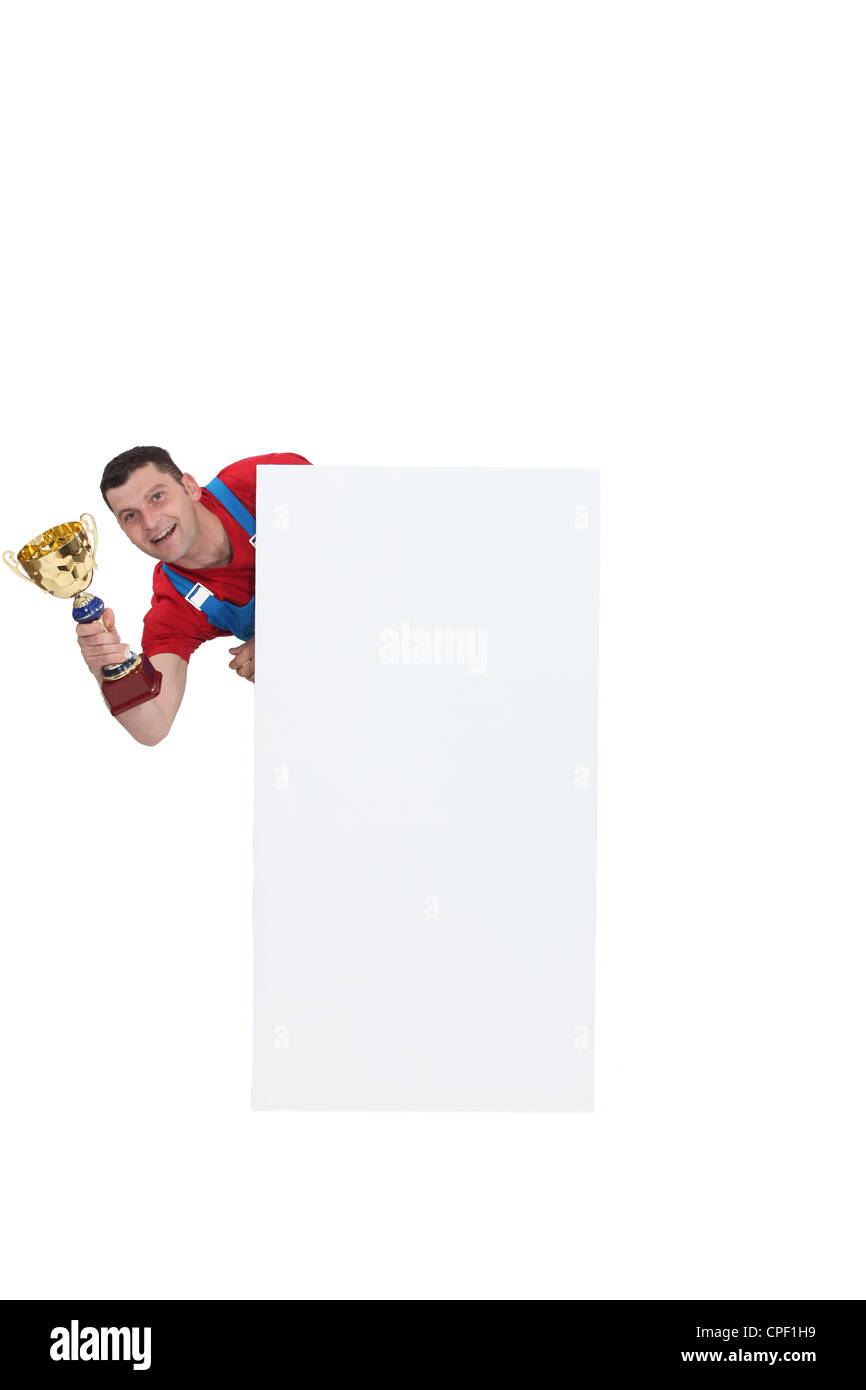 Man holding a trophy behind a white blank square - Stock Image