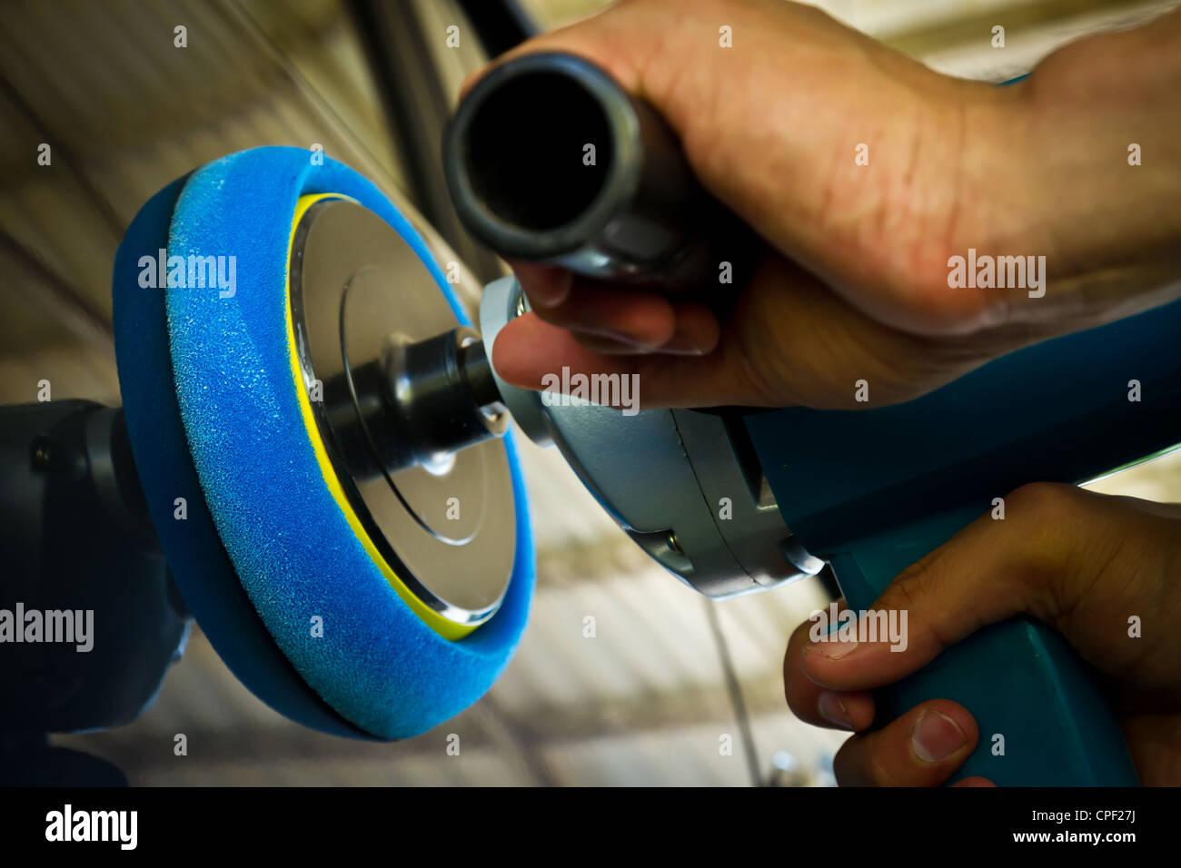 Hand holding car polisher - Stock Image
