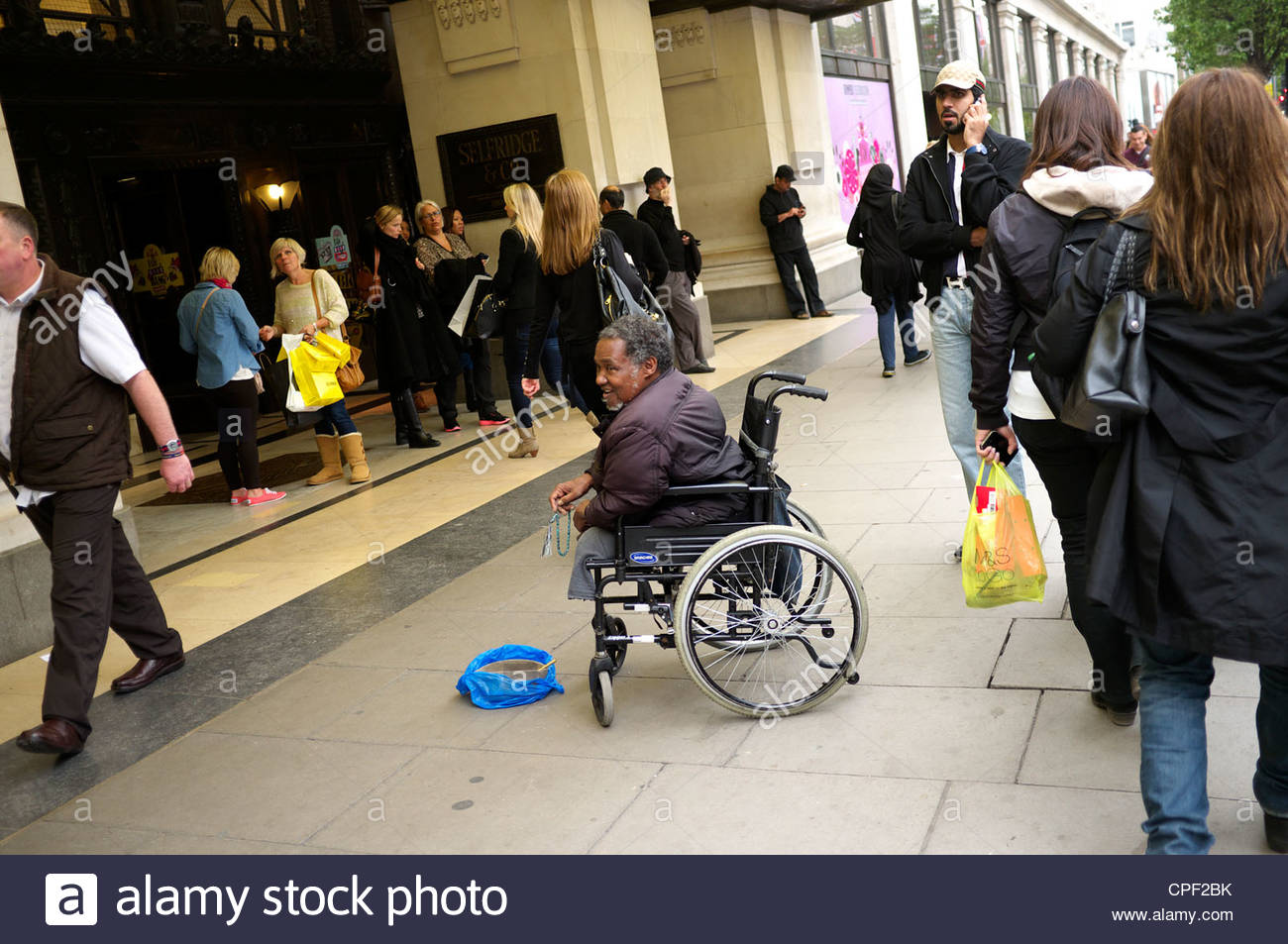 Entrance to the Selfridges store in London's Oxford Street, with a disabled beggar in a wheelchair outside. - Stock Image