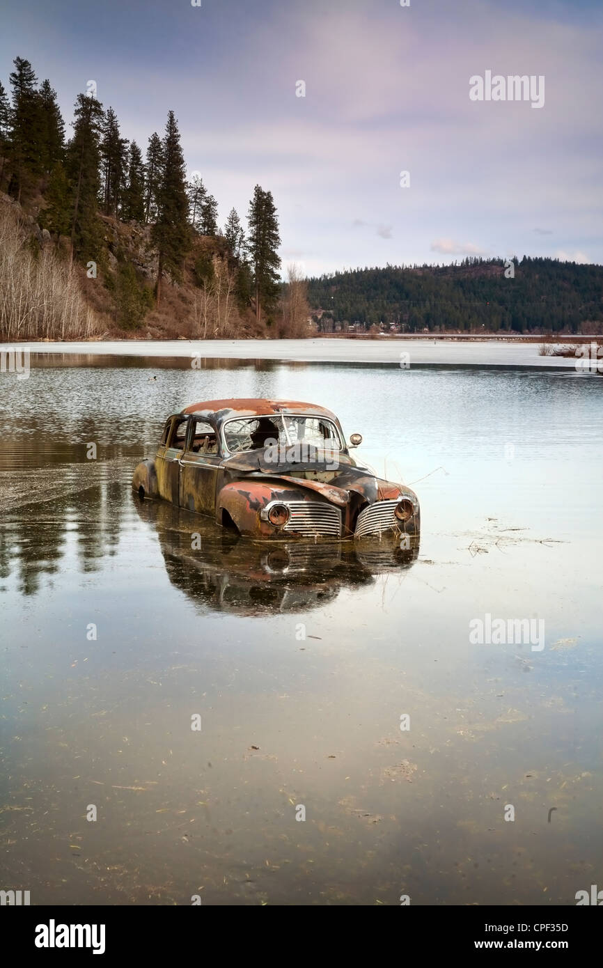 An old antique car sits swamped in a flooded pond. - Stock Image