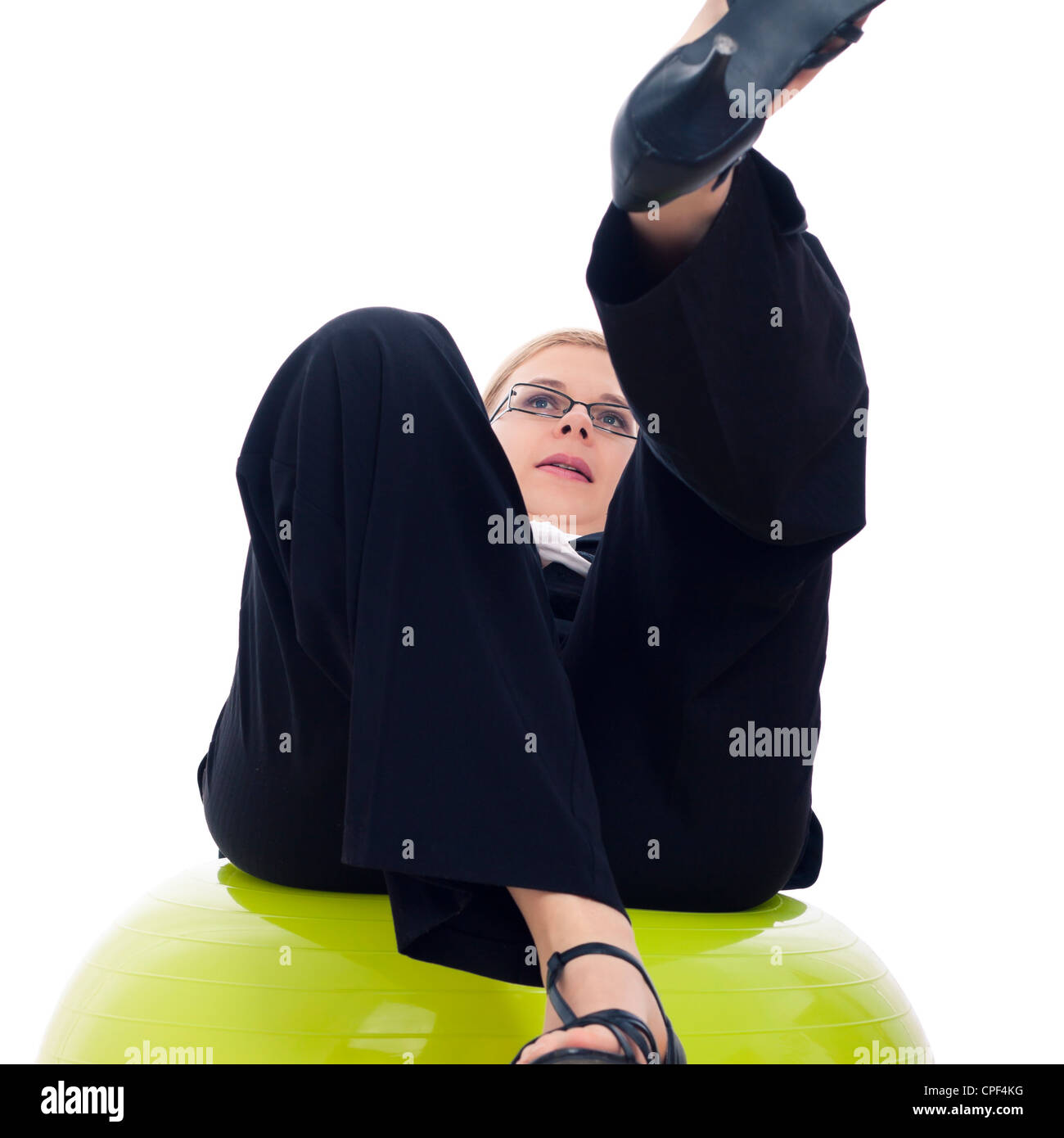 Businesswoman falling down from green exercise ball, isolated on white background. - Stock Image