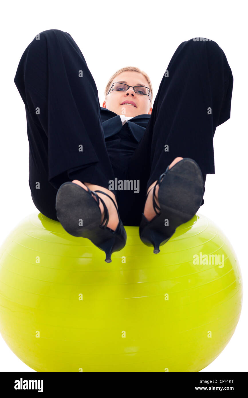 Businesswoman having fun on green exercise ball, isolated on white background. - Stock Image