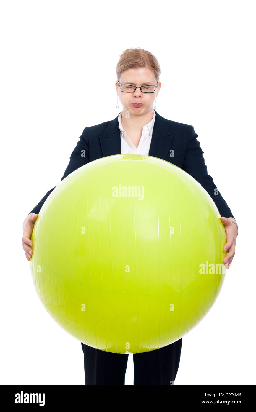 Funny bloated businesswoman holding green exercise ball, isolated on white background. - Stock Image