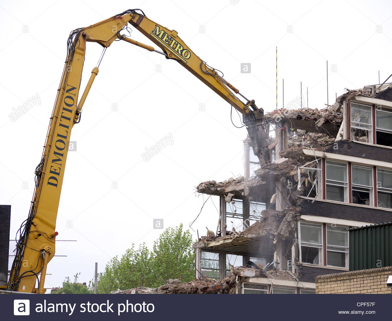 Demolition of an old building by heavy machinery - Stock Image