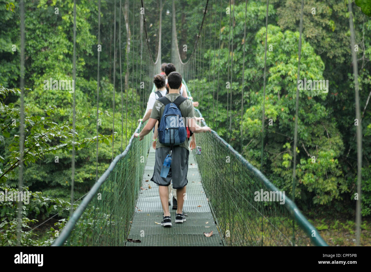 Teenagers in rainforest Costa Rica crossing a river on a suspended cable bridge - Stock Image