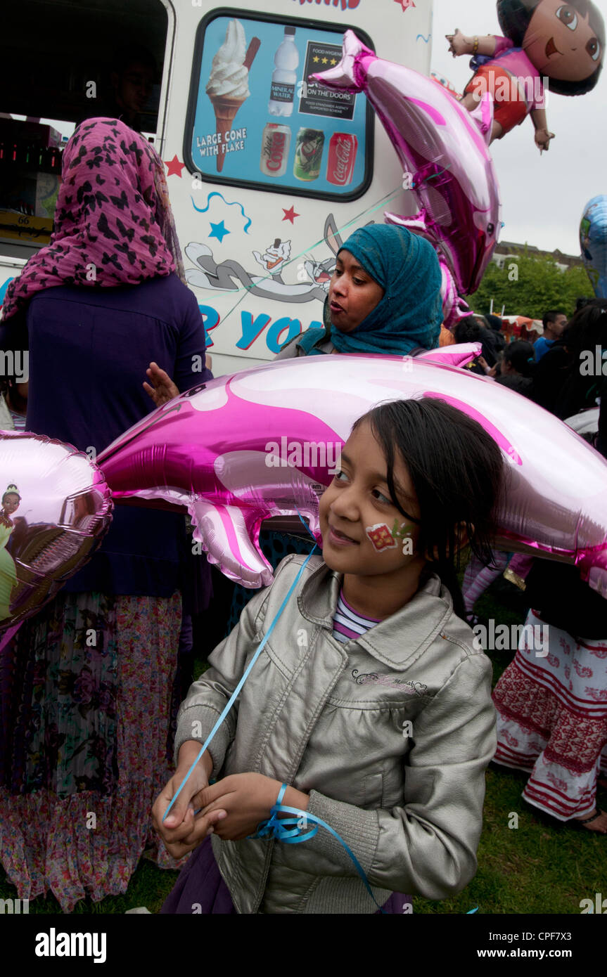 Boishakhi Mela, celebration for Bangladesh New Year. Family with pink dolphin balloons buying ice-creams - Stock Image
