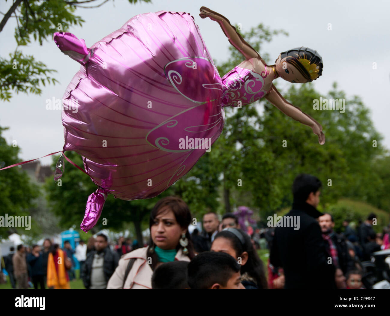 Boishakhi Mela, celebration for Bangladesh New Year. Pink ballet dancer balloon over crowd of local Bangladeshis - Stock Image