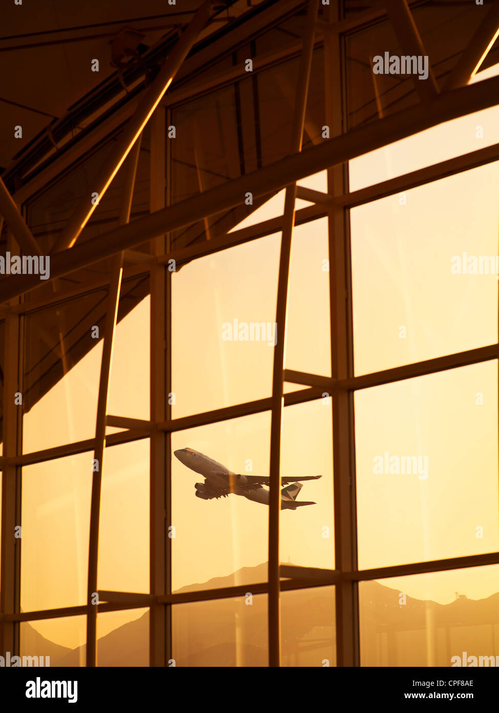 A sunset view of airplanes taking off at the Hong Kong International Airport on New Years Eve. December 31, 2010. - Stock Image