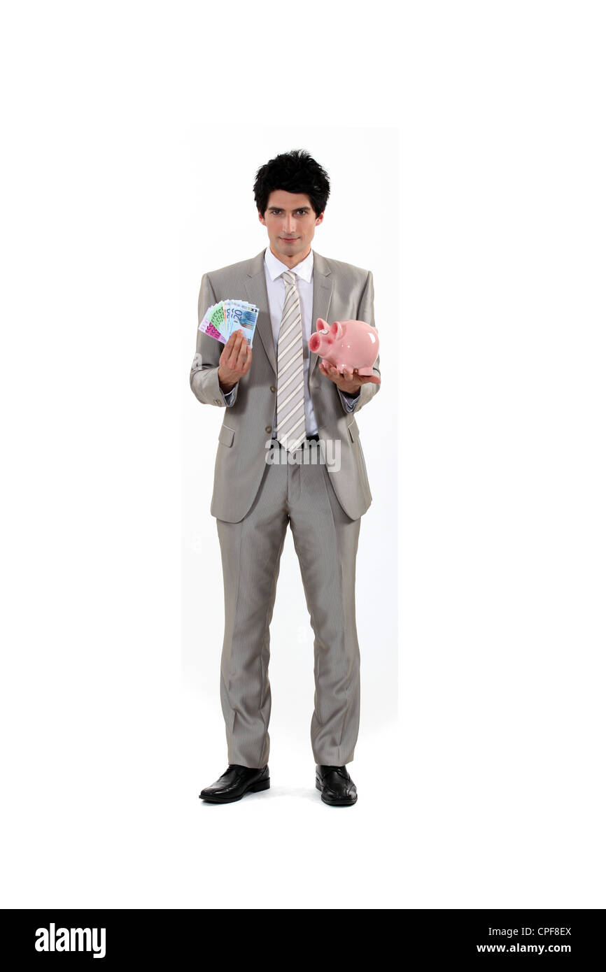 Man saving his money in a piggy bank - Stock Image