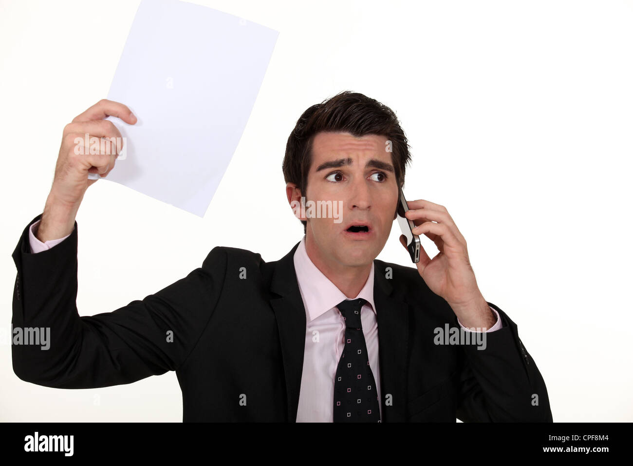 businessman having a surprising news on his cell - Stock Image