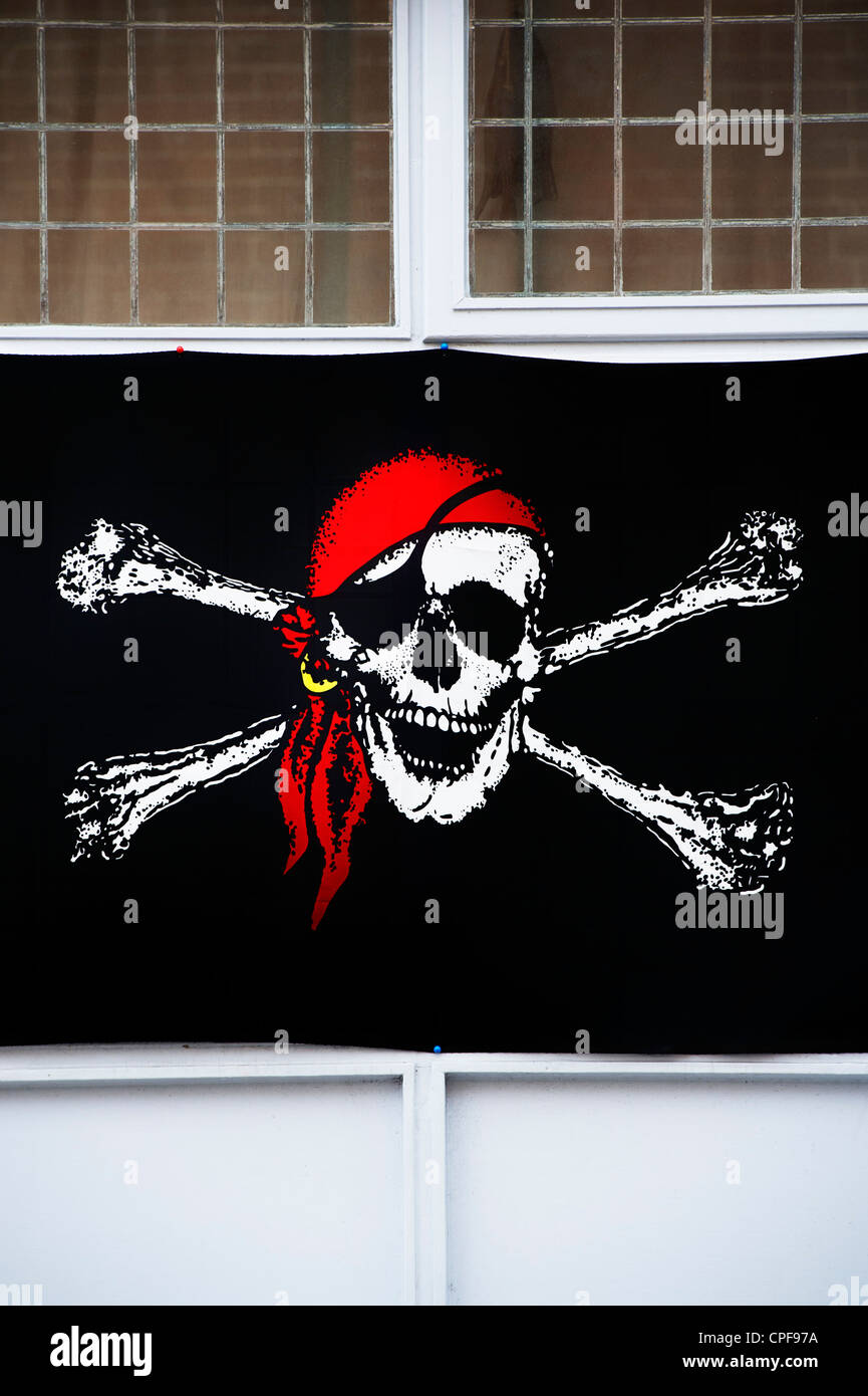 Jolly Roger pirate flag in bar window, Brixham, Devon, England - Stock Image