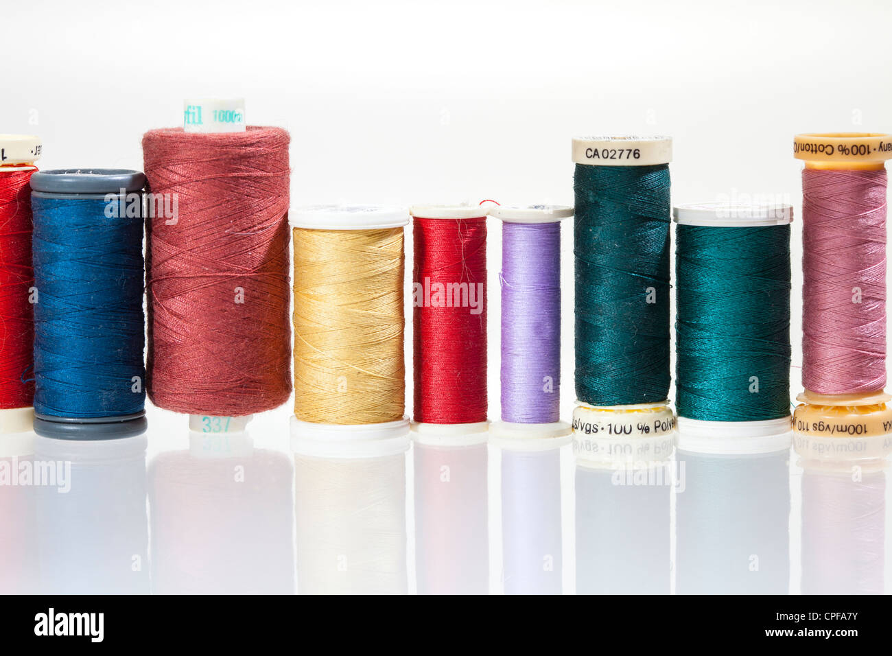 Sewing threads on bobbins in different colours - Stock Image
