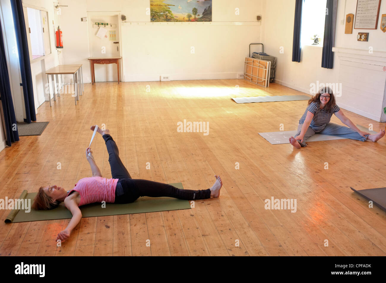 Two women warm up before a yoga class held in a village hall in Cornwall, UK - Stock Image