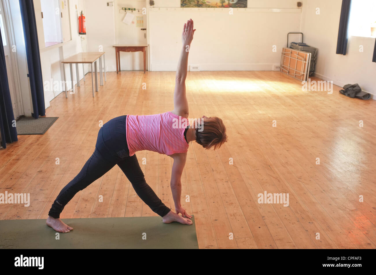 A woman in her mid forties warms up before a yoga class held in a village hall in Cornwall, UK - Stock Image