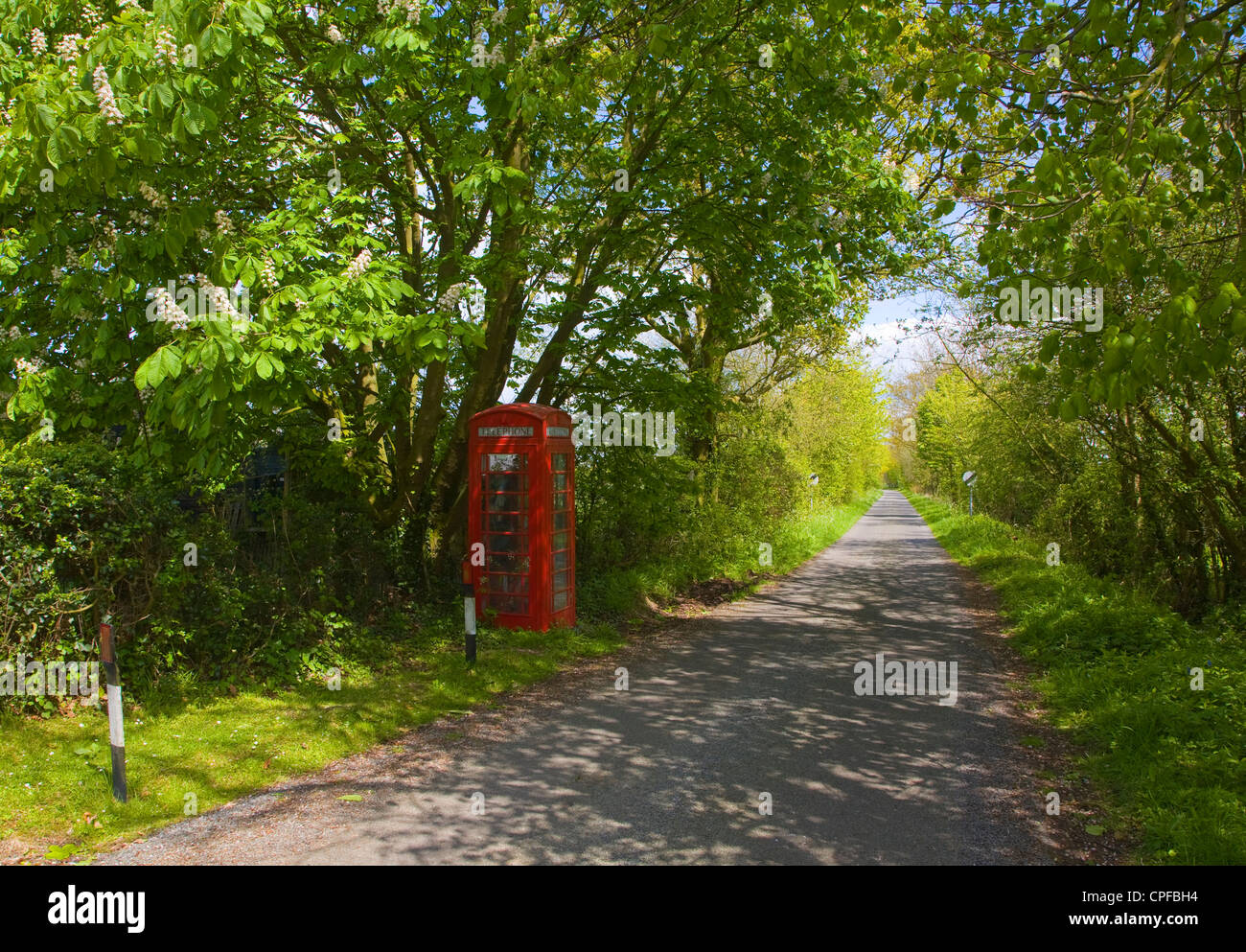 Traditional red telephone box booth in countryside - Stock Image