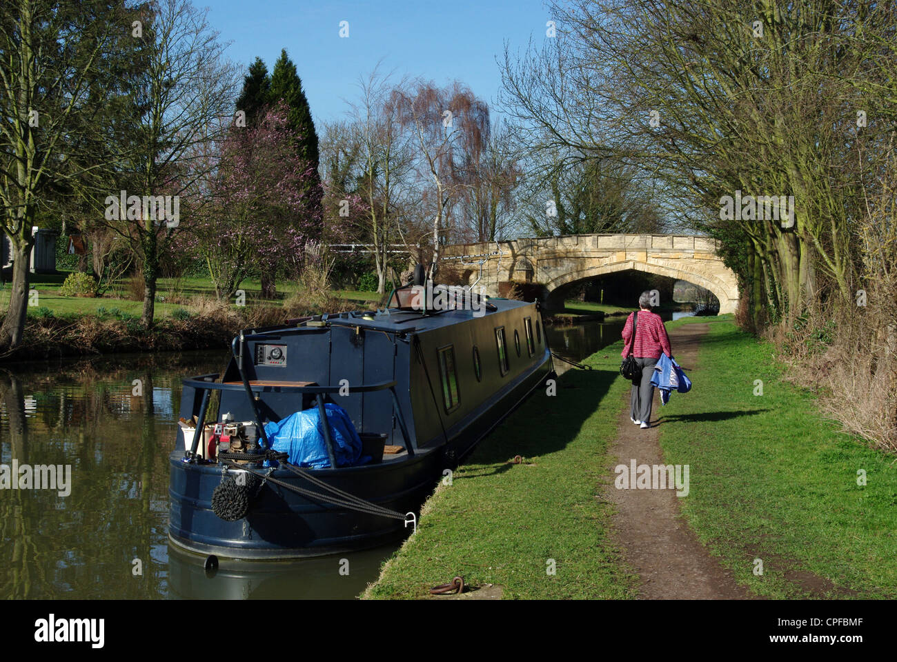 Woman walking along the canal towpath at Cosgrove, with Solomon's Bridge in the background. - Stock Image