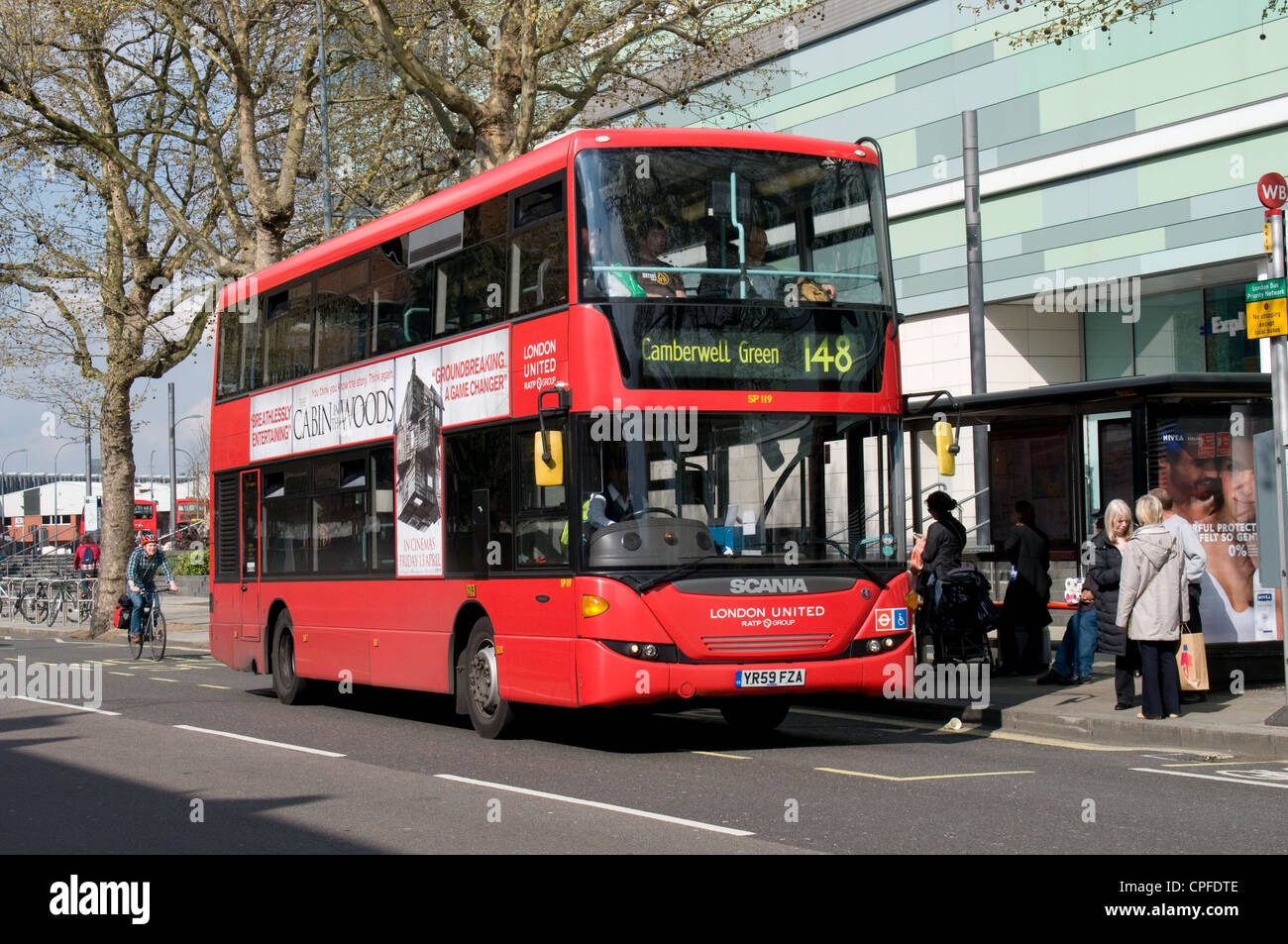 A Scania Omnidekka double deck bus operated by London United picks up passengers outside the Westfield shopping Stock Photo