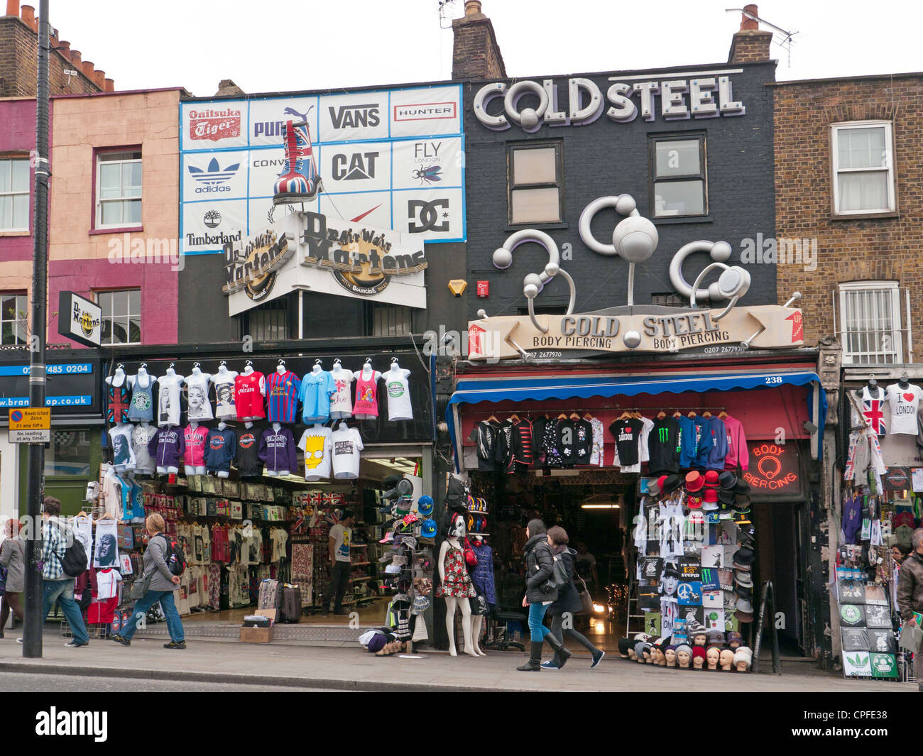 Shoppers and tourists viewing boutiques in a street in Camden Market, London, UK - Stock Image