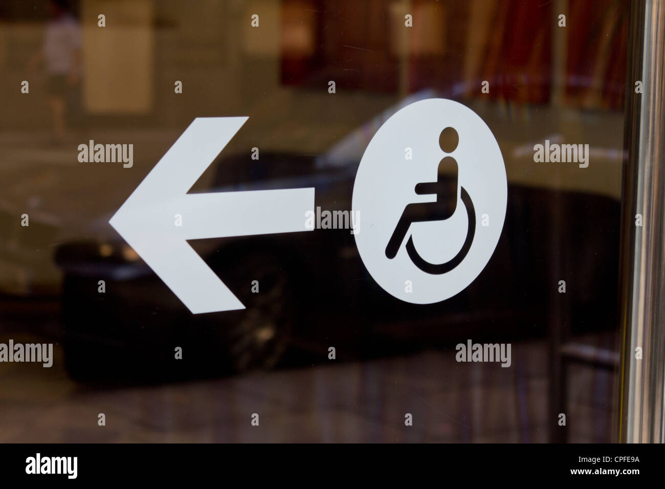 A disabled access sign on an office window - Stock Image