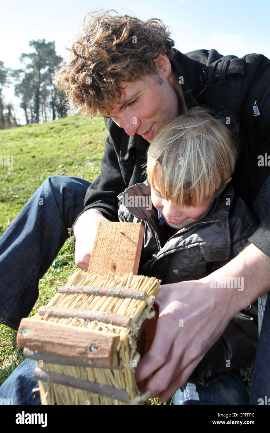 Father and son constructing hut for birds - Stock Image