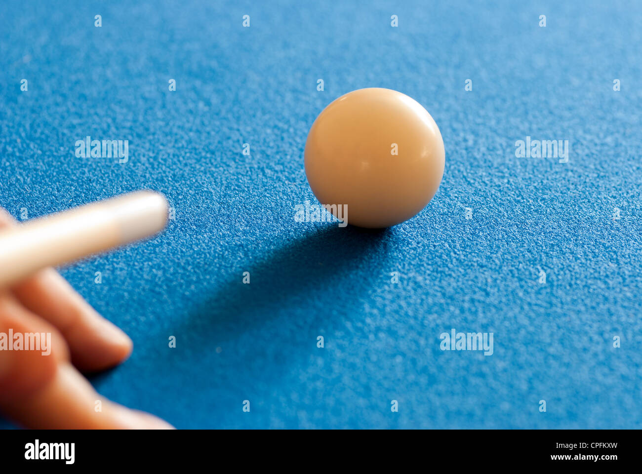 Pool cue about to strike a cue ball - Stock Image