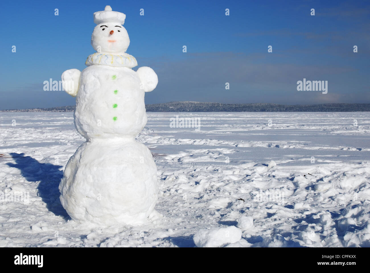 snowman on a wintry sunny day against blue sky - Stock Image