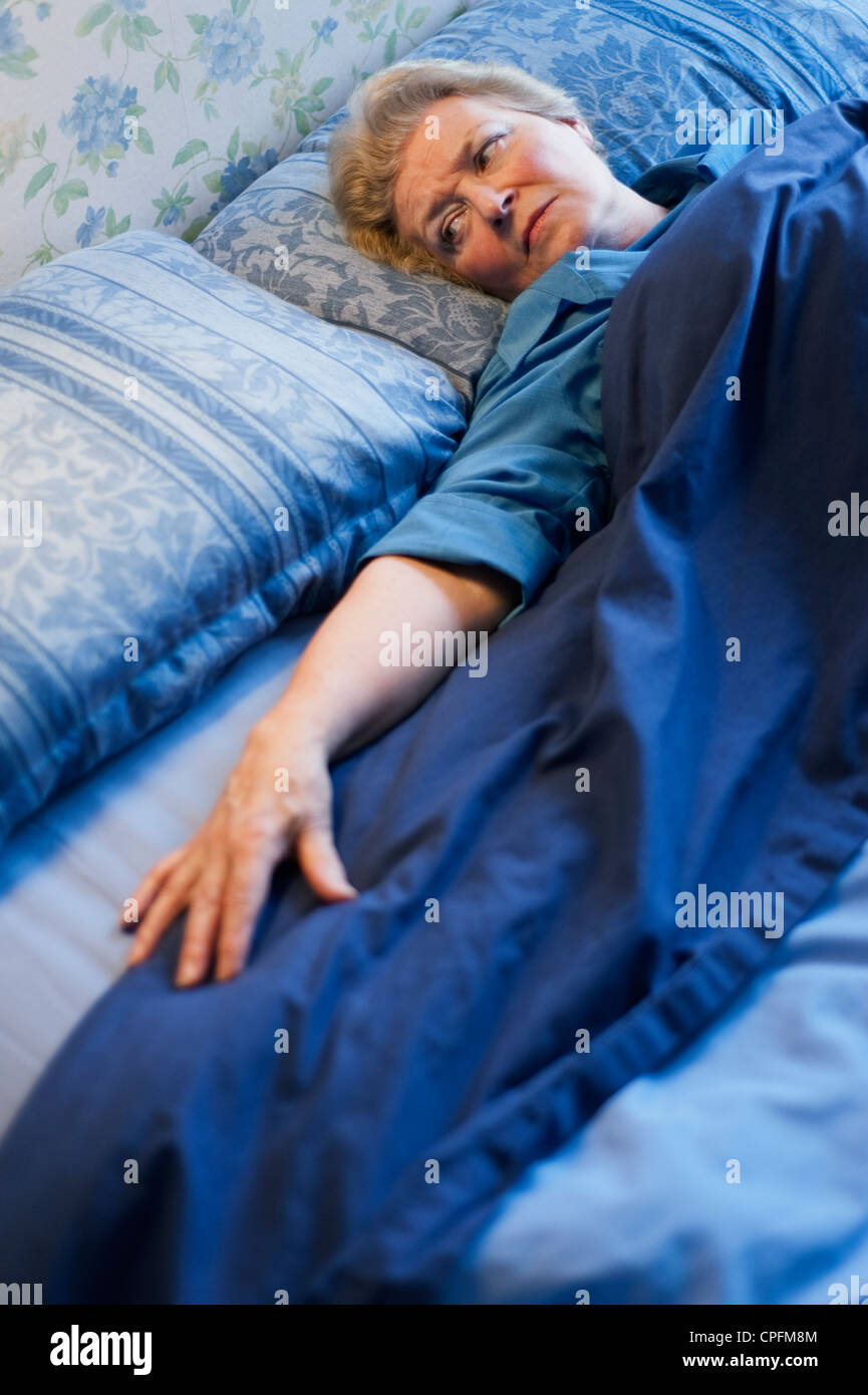 Mature woman lying in bed and looking at the empty space next to her - Stock Image