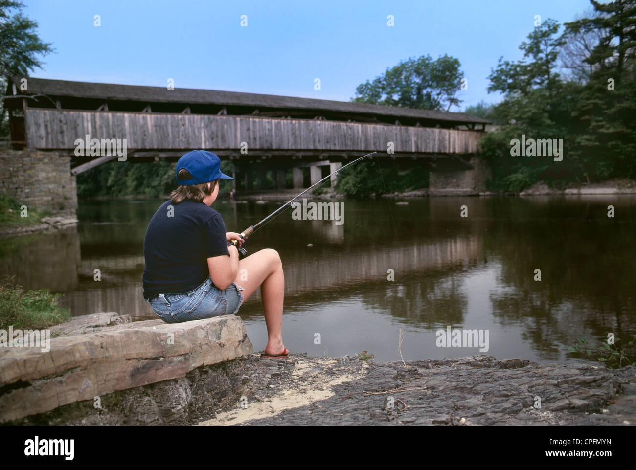 Boy Fishing in River - Stock Image