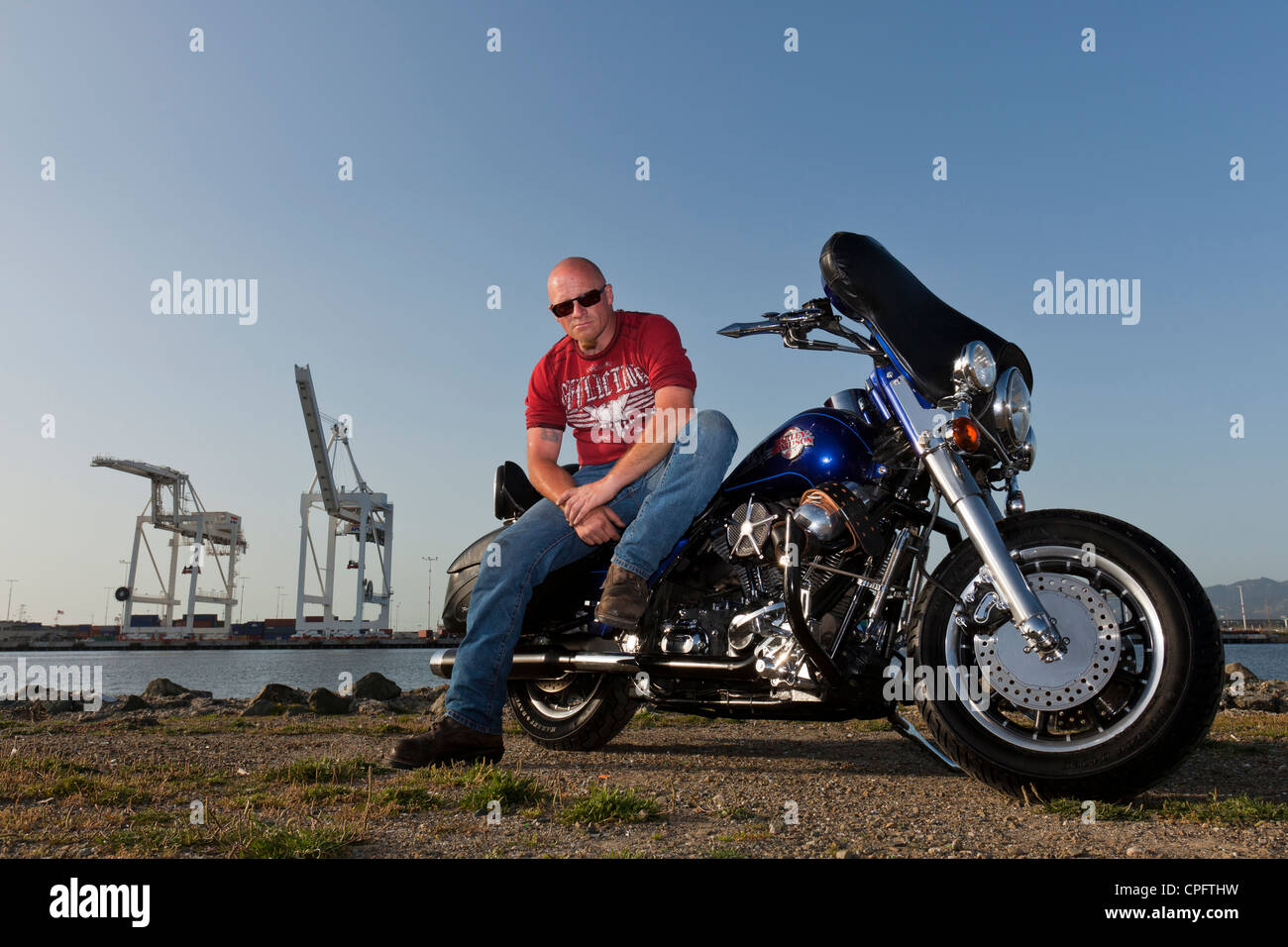 A Harley Davidson motorcyclist sitting on his bike - Stock Image