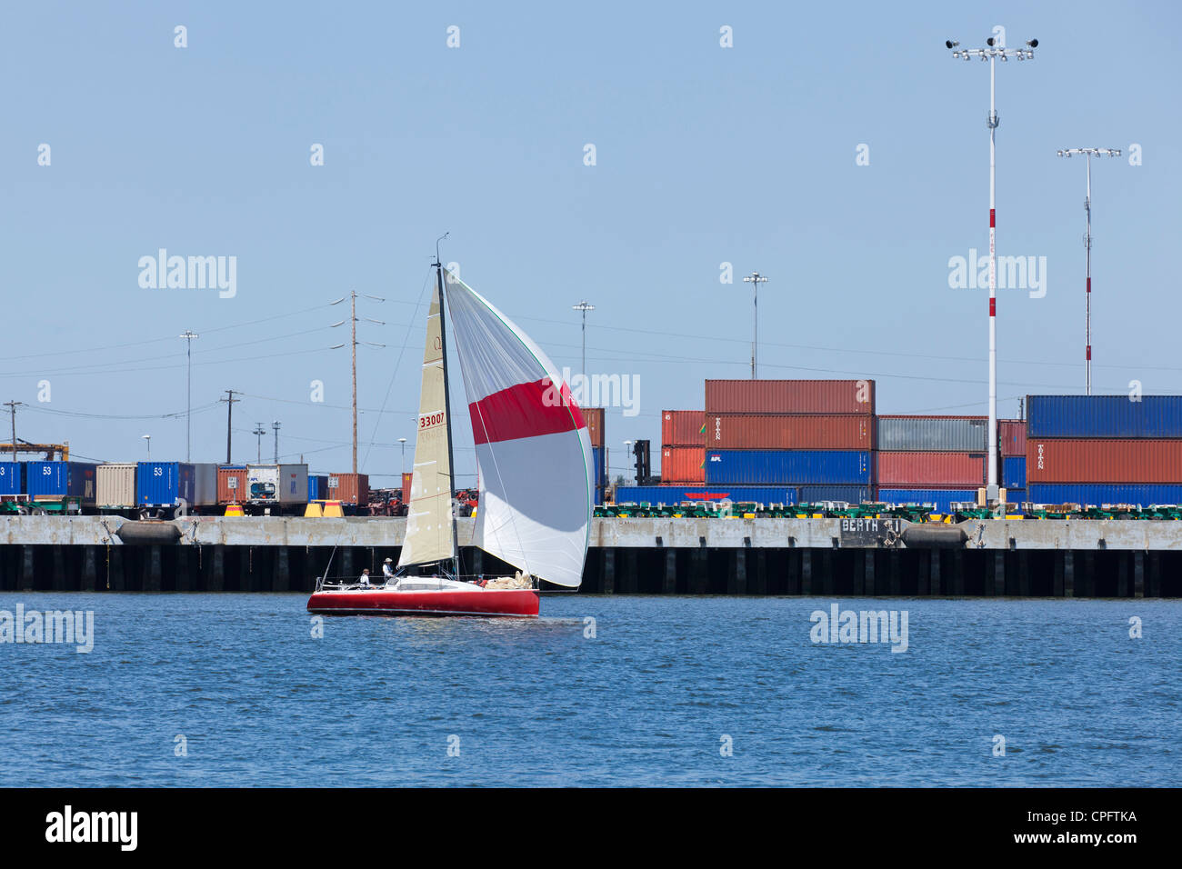Sailboat in industrial harbor - Stock Image