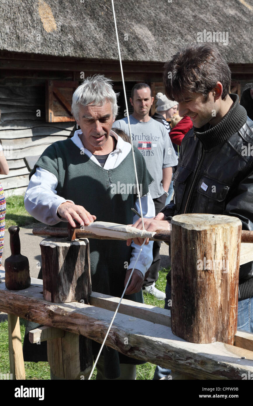 Craftsman teaching a man how to use a pole lathe, Bede's World, Jarrow, North East England, UK - Stock Image