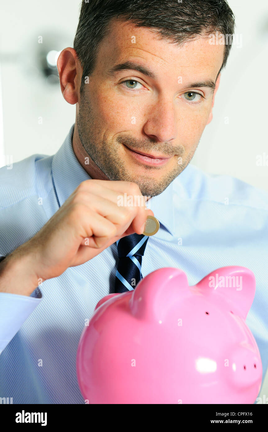 businessman matting a coin in the piggy-shaped pink pig - Stock Image
