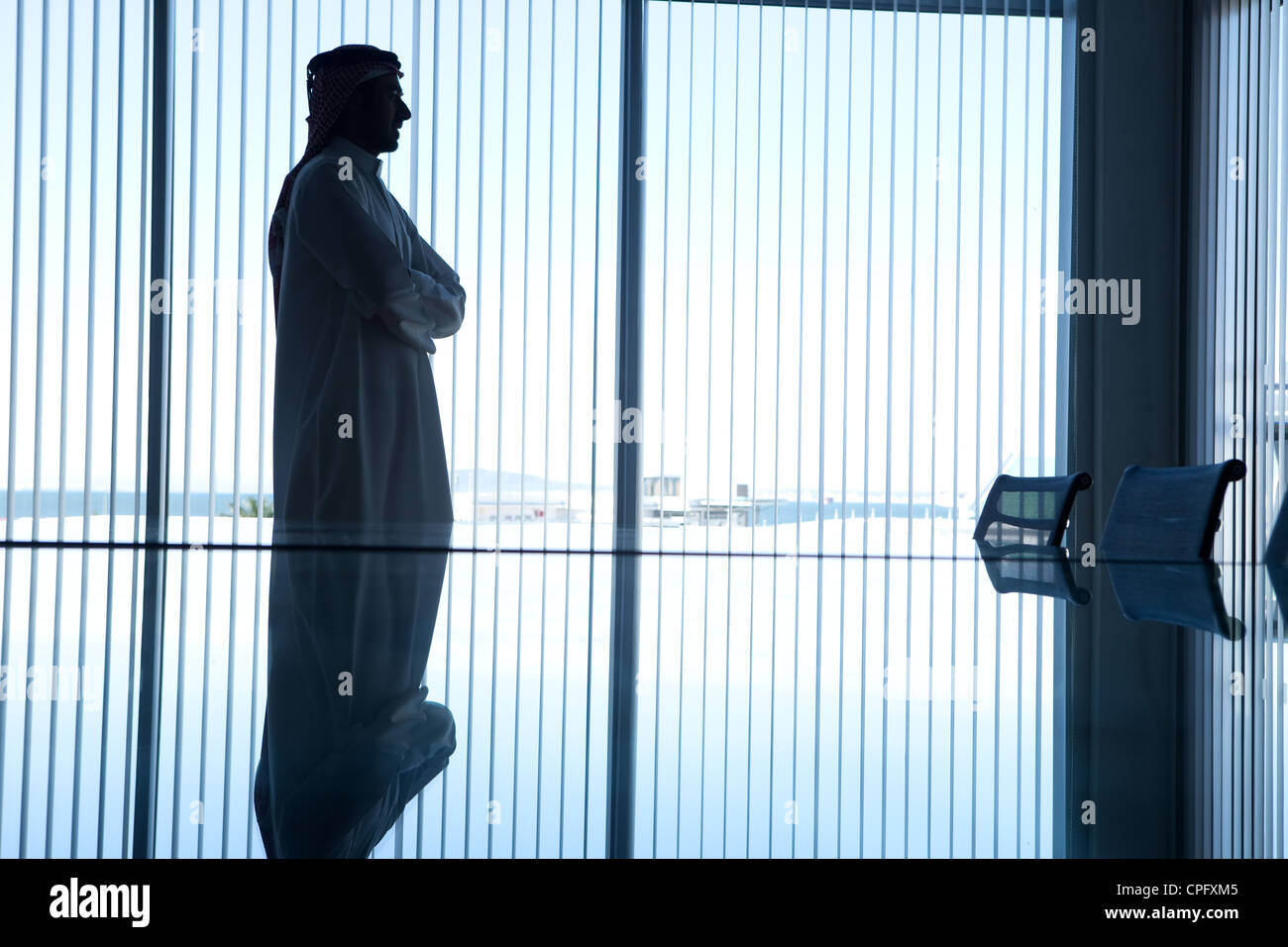 Silhouette of an arab businessman with arms crossed standing in a conference room. - Stock Image