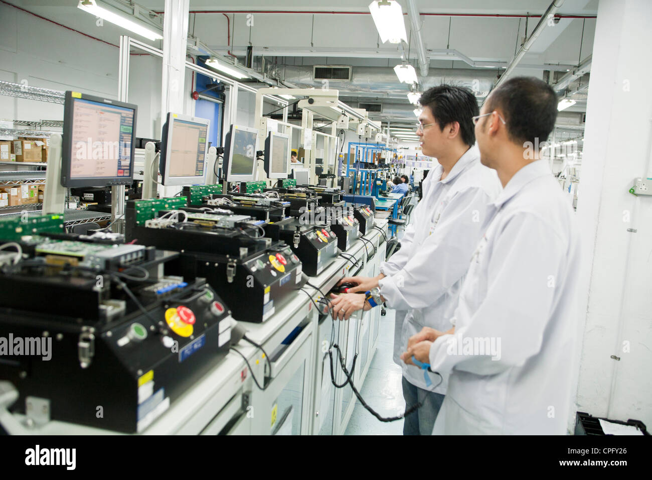 Workers assemble hand-held inventory computer devices on the assembly line at the Venture Corp. factory in Singapore - Stock Image