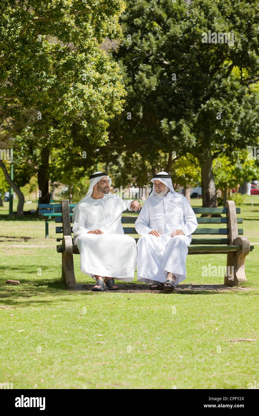 Arab father and son sitting together on a bench at the park. - Stock Image