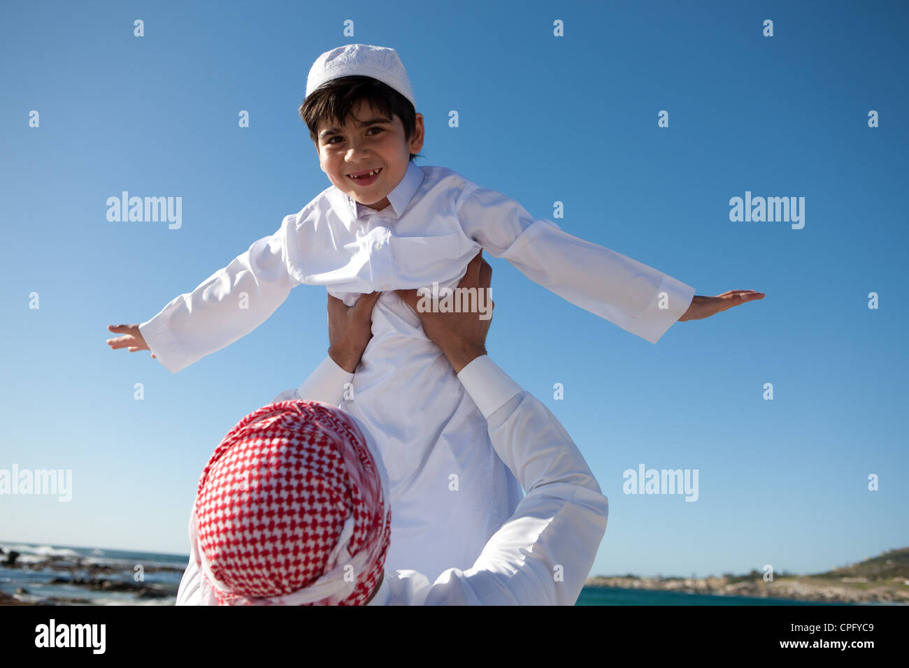 Portrait of arab father lifting his son on beach, boy arms raised. - Stock Image
