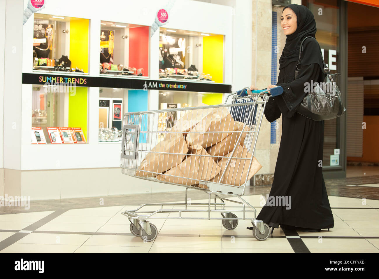 Arab woman with shopping cart walking at the mall, smiling. - Stock Image