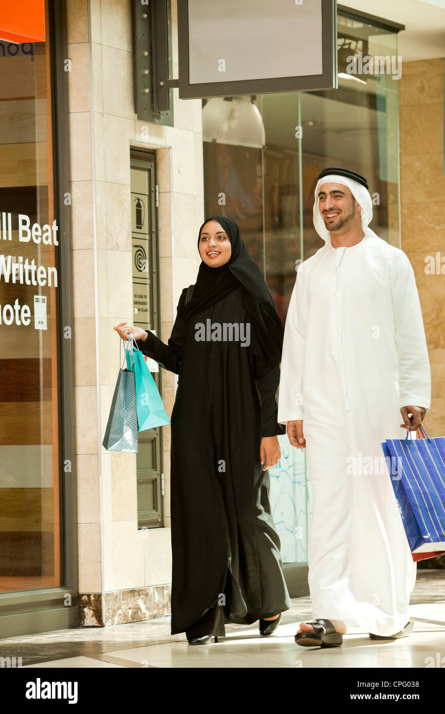 Arab couple with shopping bags walking in the mall. - Stock Image