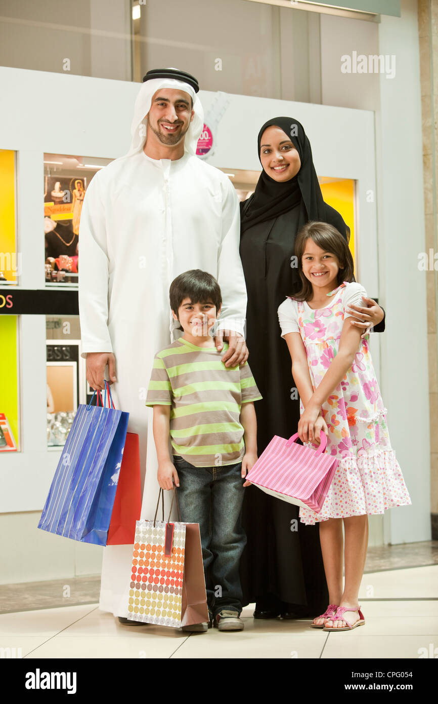 Portrait of arab family standing in the shopping mall, smiling. Stock Photo