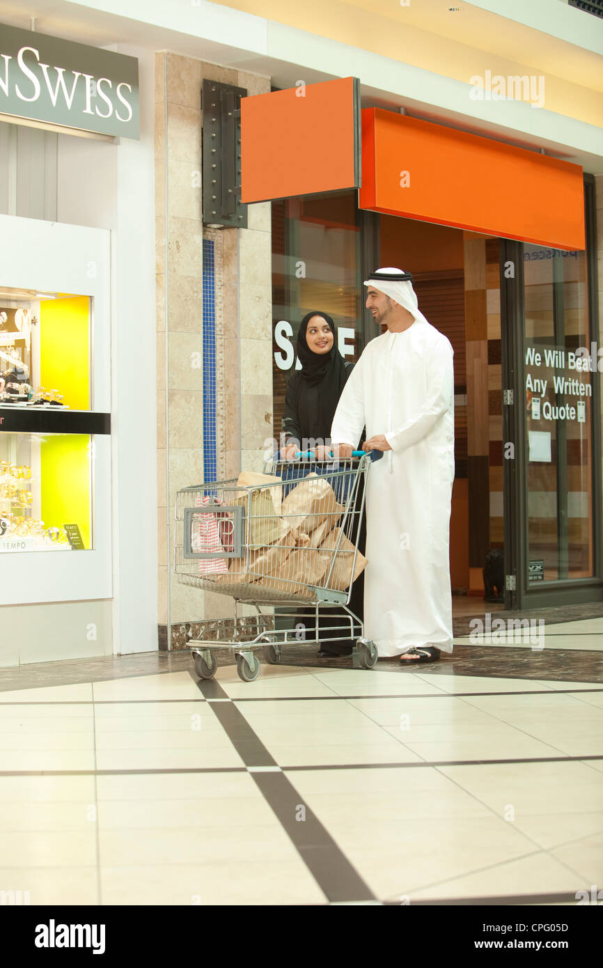 Young arab couple with shopping cart walking in the mall. - Stock Image