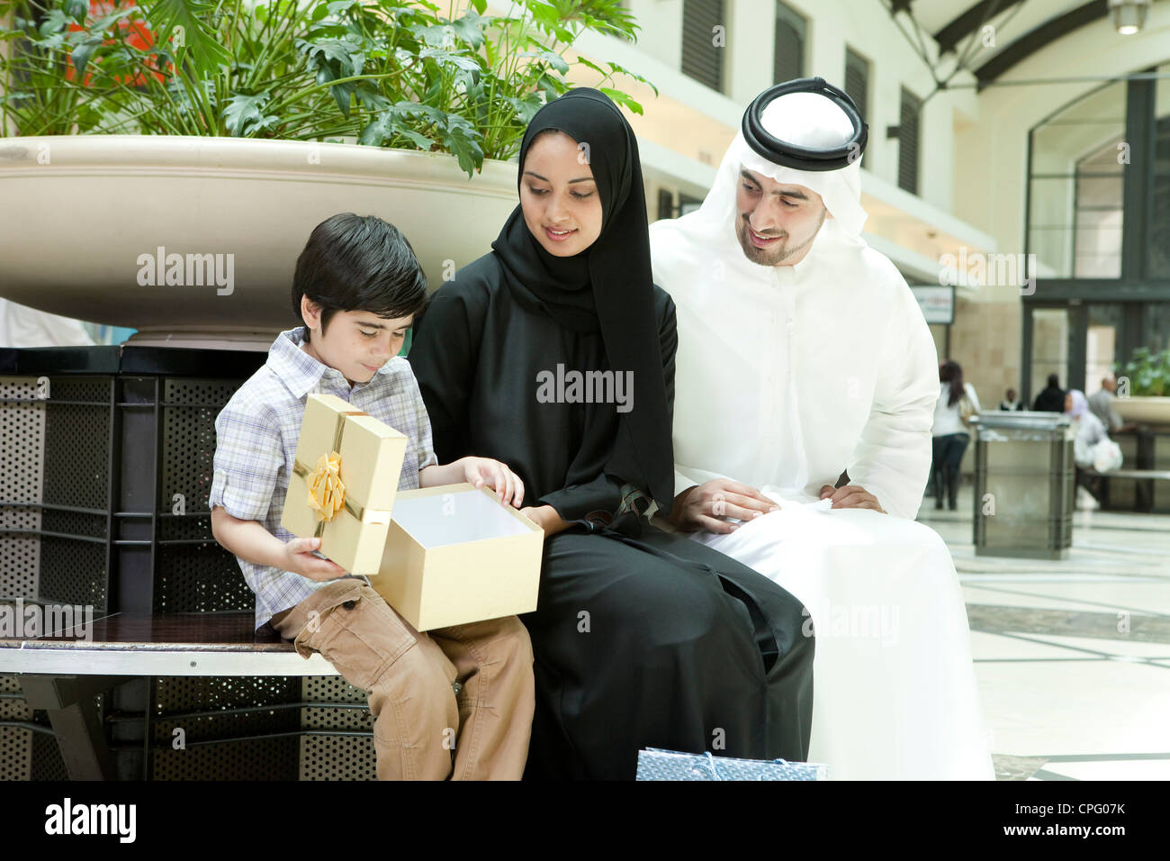 Arab family sitting at the shopping mall, parents giving gift to their son. - Stock Image