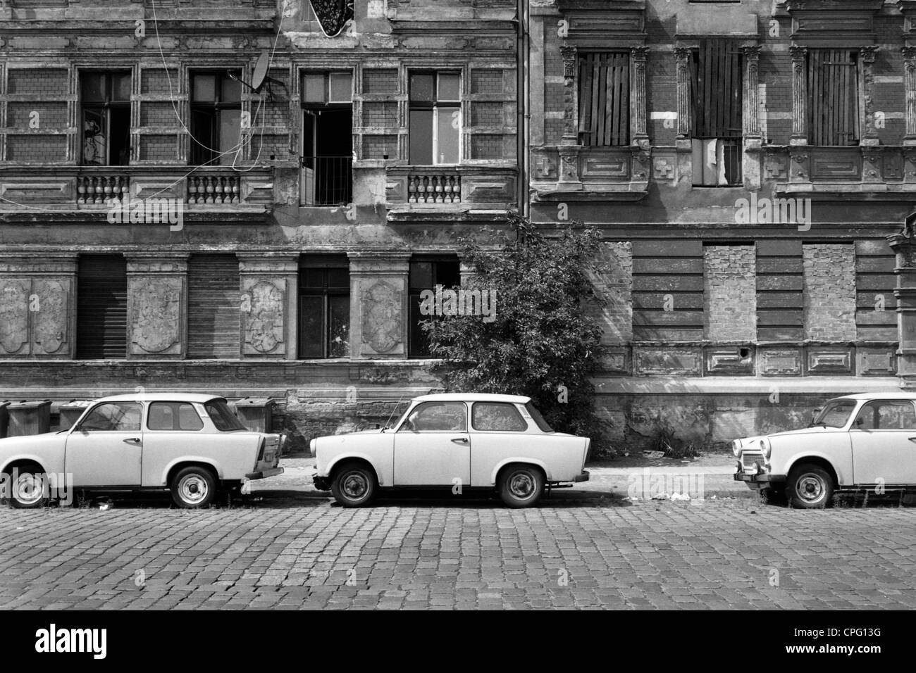 Three Trabants parked in front of a run-down old building, Berlin, Germany - Stock Image