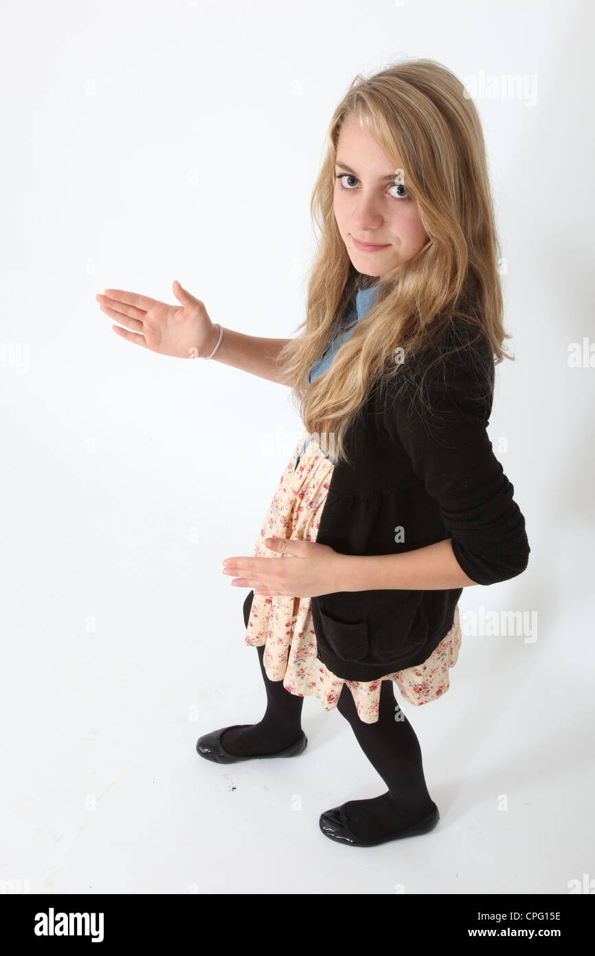 Young teenage girl standing looking at camera hands in a robotic motion - Stock Image