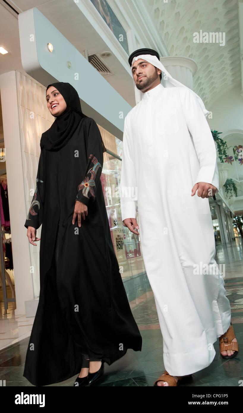 Arab couple walking in shopping mall. - Stock Image