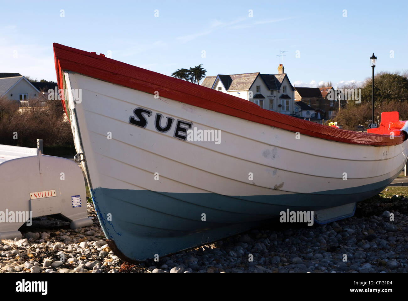 A small rowing boat named SUE on a pebble beach - Stock Image